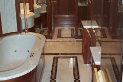 Bagno con pavimenti intarsiati in marmo Bianco Statuario, Giallo Siena e Sodalite